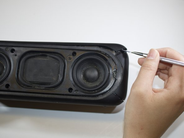 With the Sony logo facing towards you, use the medium spudger to lift the side plates from the internal frame.