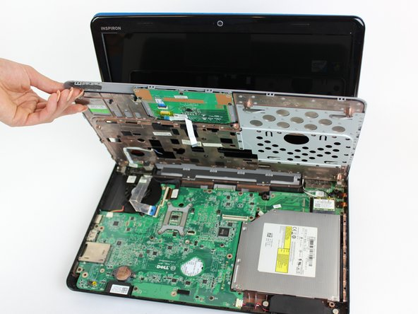 Lift the cover upwards and away from the body of the laptop, after removing the optical drive and unscrewing the three screws on the right