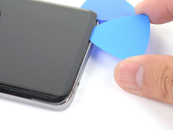Slide an opening pick along the bottom edge to slice through the adhesive.