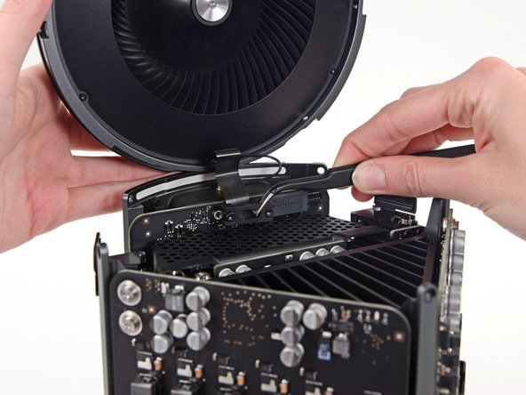 Use a pair of tweezers to pull the fan cable bracket away from the fan assembly.
