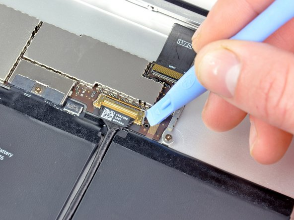 Flip up the retaining bar securing the upper component board cable connector.