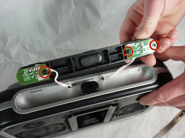 Using a Phillips #1 screwdriver, remove the two 7mm screws that hold the volume button circuit board to the control panel.