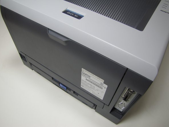 Located on the back of the printer, open up the cover by grabbing onto the tab and pulling down.