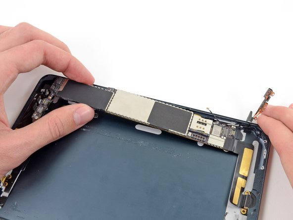 Once all of the adhesive is broken and the logic board is free, gently lift it up from the top.