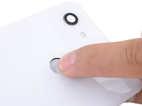 From the outer side of the back panel, use your finger to push the fingerprint sensor out of its cutout.