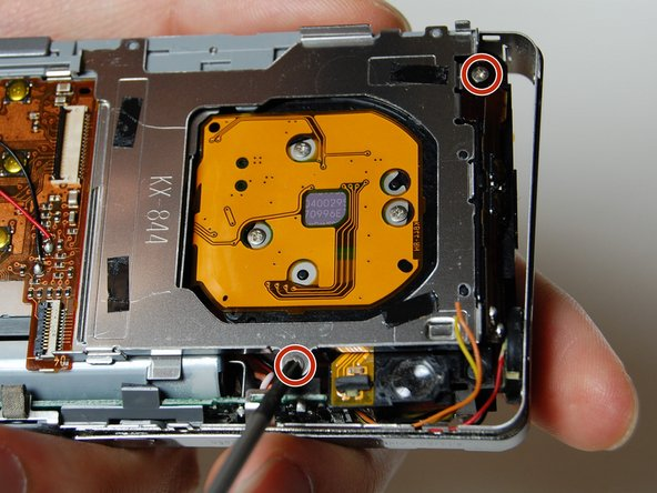 Use your Phillips #00 screwdriver to remove the two screws connecting the frame to the back of the camera.