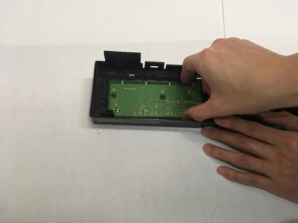 Grip the circuit board and slide towards the front side of the plastic casing.