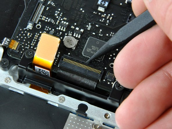 Using the tip of a spudger, flip up the keyboard ribbon cable retaining flap.