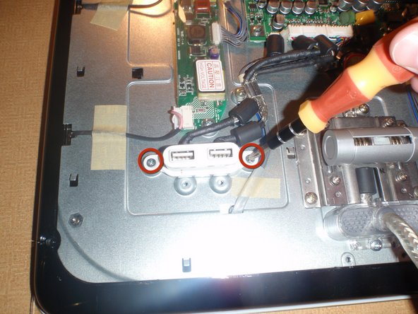 Remove the two phillips head screws on the sides of USB port, using #2 phillips head screwdriver.