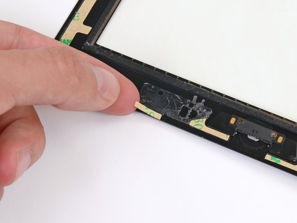 Lay the final small rectangular adhesive strip to the left of the hook-shaped adhesive strip, immediately to the right of the thin L-shaped strip, and flush with the bottom of the front panel.