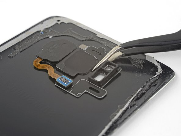 Line up the rear camera bezel with the cutouts on the rear glass, then set it down on the adhesive. Make sure the side with the camera lens cover protruding is facing the rear glass.