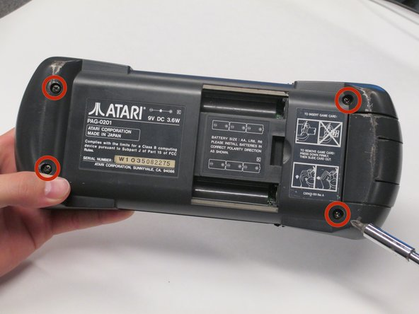 Remove the four 35 mm Phillips #1 screws at each corner of the backside on the Atari Lynx.