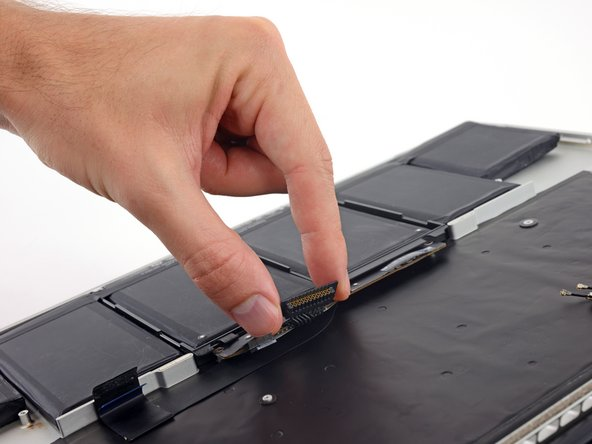 Grab the battery connector or the top edge of the plastic battery frame and lift it slightly, exposing the top edge of the two center battery cells.