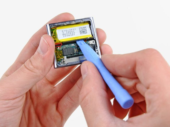 Use an iPod opening tool to gently pry the battery up from the adhesive securing it to the outer case.
