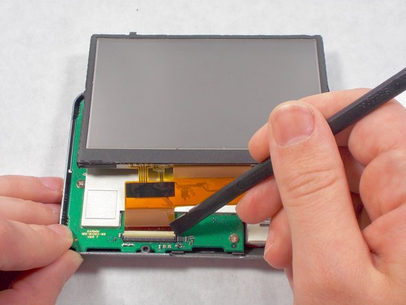 Carefully use the black spudger to lift the white retaining clamp on the display cable ZIF connector.