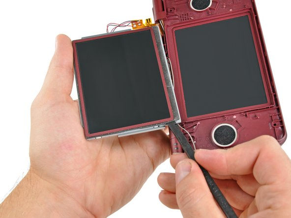 In the same manner as previously described, detach the adhesive along the left edge of the upper LCD.