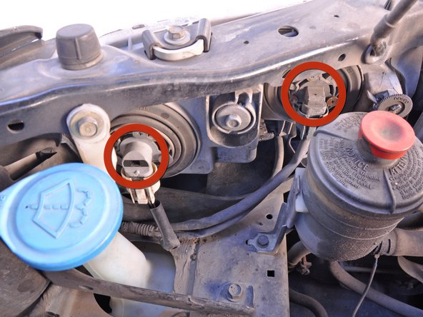 Locate the head light bulbs and connectors directly behind the headlights and on either side of the engine bay.