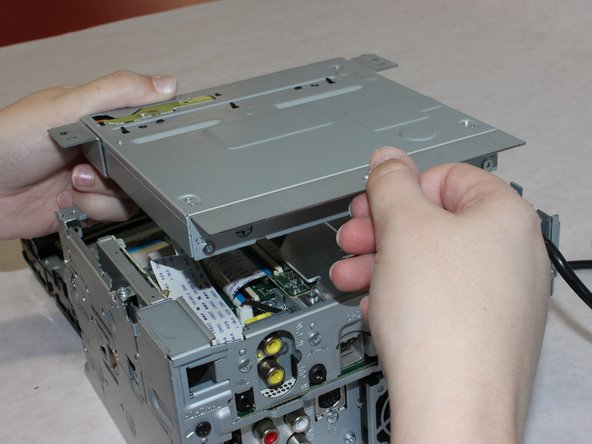 Lift the CD drive carefully to expose the attached cable underneath.