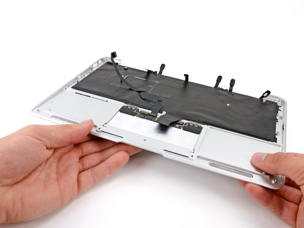 Holding the upper case up off the table with one hand, gently push the trackpad up through the upper case.
