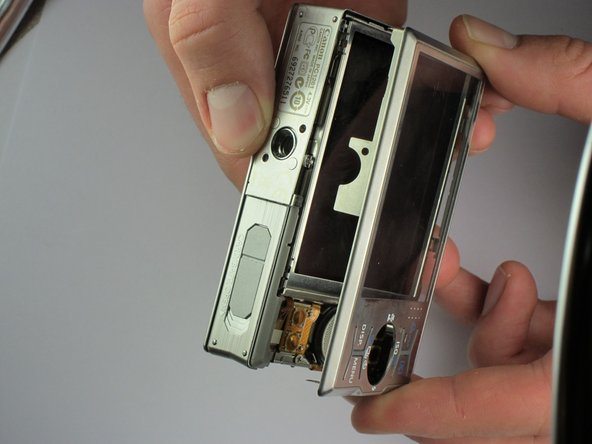 Grip the camera from the sides and carefully remove the screen cover. Start at the bottom edge and slowly lift up the cover. Pay special attention to the area with the camera/video switch.