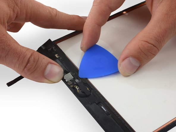 Peel up the last of the tape holding the home button ribbon cable in place by inserting an opening pick between the cable and the digitizer.