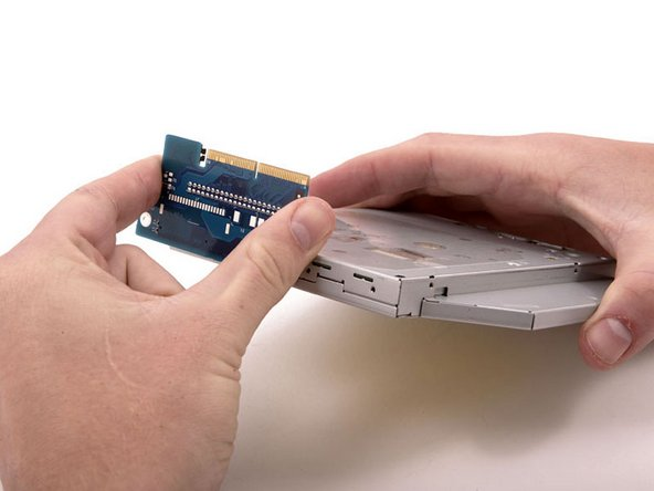 Grasp either side of the interface board and wiggle it free of the optical drive.