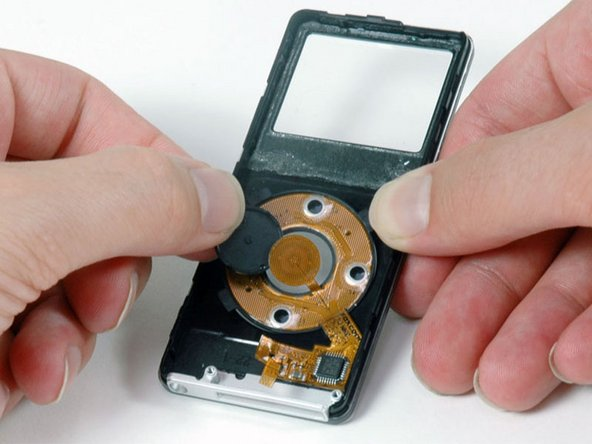 Push the click wheel button through from the front side of the iPod and lift it out of the iPod.