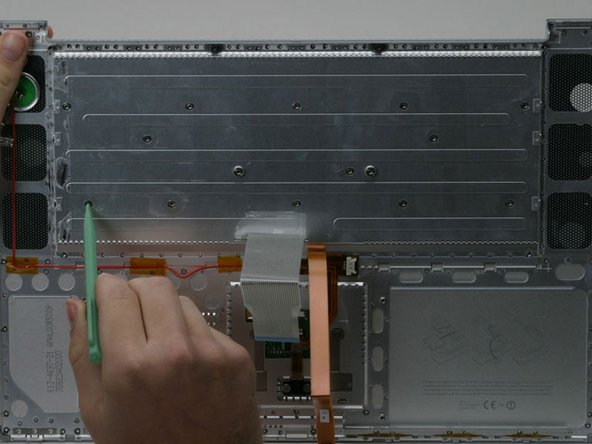 Place the upper casing on edge and use a spudger to push the keyboard away from the casing, poking the spudger through the holes where the screws were.