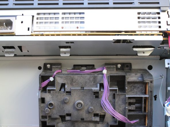 Set the printer back down and remove two more Phillips screws with integrated lock-washers, which releases the optical sub-assembly.