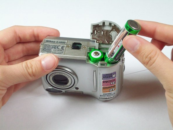 Remove the dead batteries.  The easiest way to do this is by turning the camera right side up and gently tapping the lens side of the camera against your hand until they fall out.  If this does not work, you can simply pull them out.