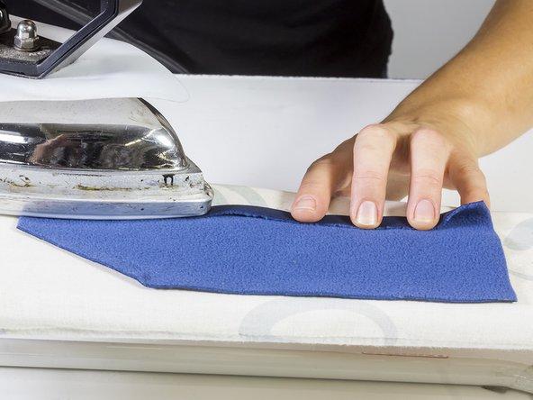 Nahtzugabe mit dem Bügeleisen umbügeln; das erleichtert das Annähen.