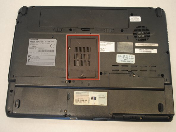 Identify the rectangular plastic RAM cover located in the bottom part of your laptop.