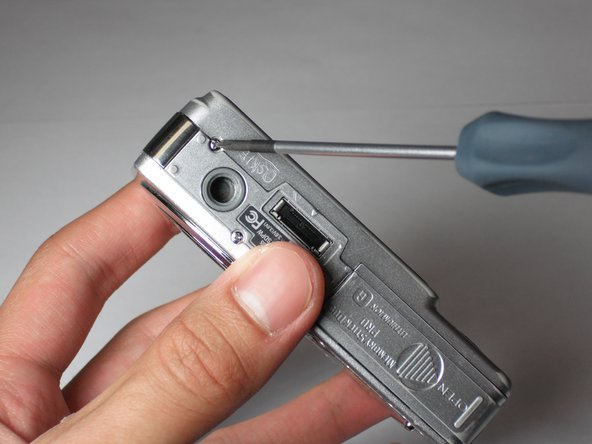 Remove the screw using the Phillips #00 screwdriver from the bottom of the camera, closest to the back cover.