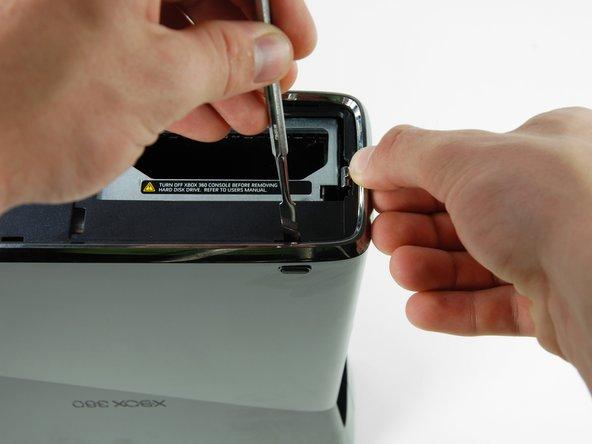 Insert a metal spudger through the slit near the rear left corner of the bottom bezel.
