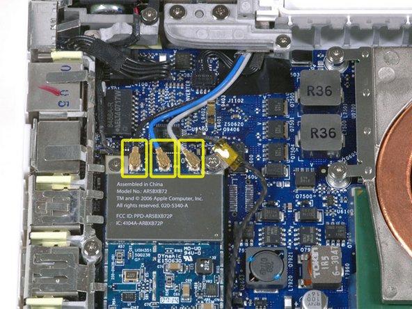 MacBook本体の左端にあるAirMac Extremeカードから3つのアンテナケーブルを外してください。下の記述に従って上へとそっとまっすぐ抜いて外してください。