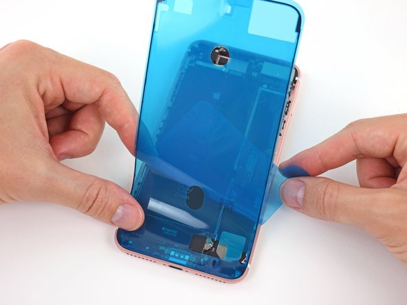 Continue peeling away the backing from the adhesive, gently pressing the adhesive into place from the bottom of your iPhone to the top.