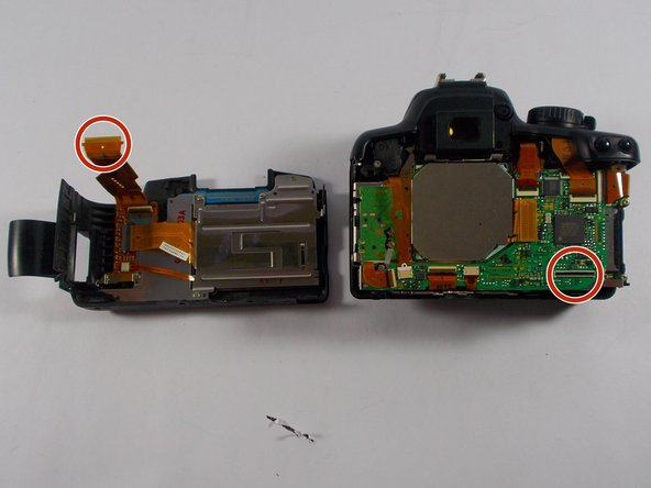 Once you have detached the back cover, use a pair of tweezers to lightly pull on strap found connecting the back cover to the camera.
