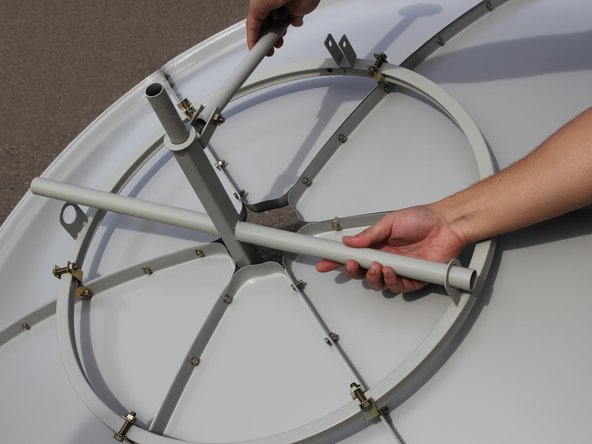 Slide the cross bearer into the two holes in the support ring making sure the top of the cross sticks through the center of the solar panel dish.