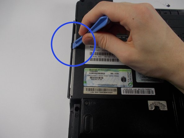 Insert the plastic opening tool into the gap between the disk drive and the laptop and pop out the disk drive.