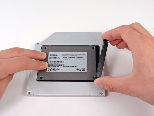 Once the hard drive is snug, reinsert the plastic positioner while holding the hard drive against the bottom of the enclosure.