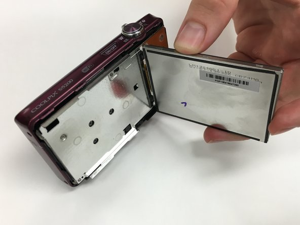 Carefully remove the LCD screen from the silver plate that once held it in place by pulling it away from the internal components