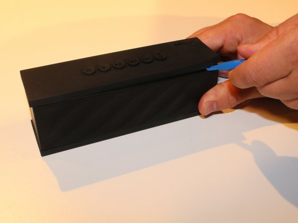 Using Blue Plastic opening tool pry the top rubber cover, then using the same tool remove the bottom panel