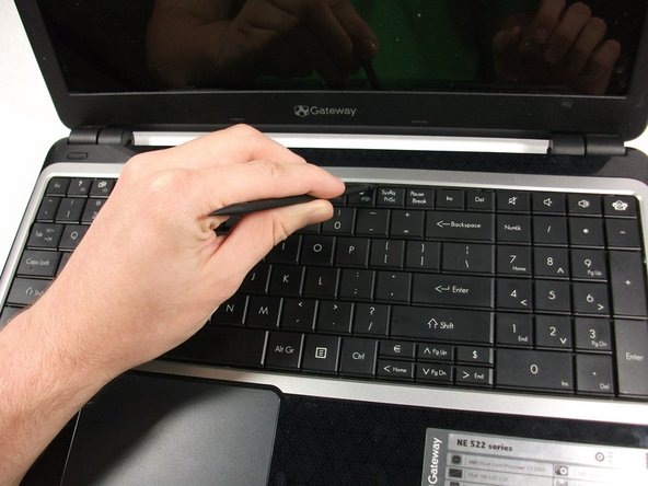 Take the plastic spudger and pull up the tabs on all four sides of the keyboard molding.