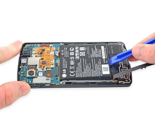 Use a plastic opening tool to pry the battery out of its housing.