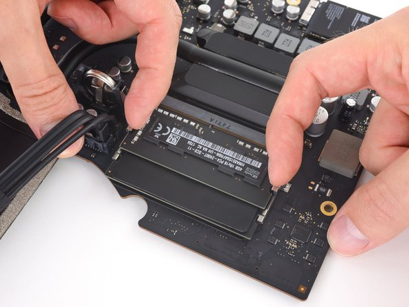 Two clips secure the RAM module in place, one on each side. Using your fingers, spread the clips away from the RAM module.