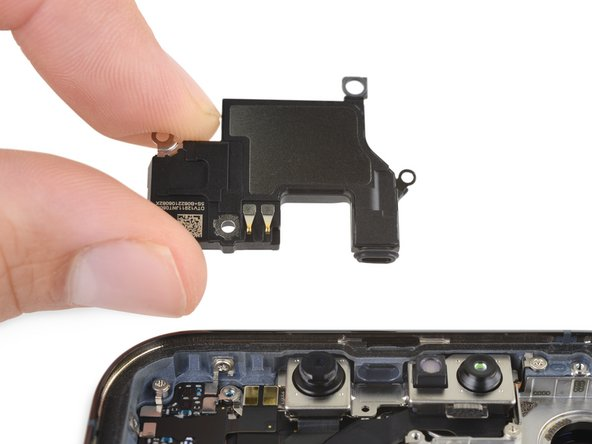 Up top we find the relocated earpiece speaker, complete with a cute little snoot. That snoot lives between the front-facing camera and Face ID hardware, and connects to a channel that directs sound out the top of the display.
