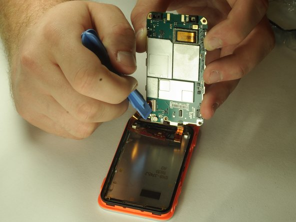 Carefully pry up on the tab holding down the display ribbon cable and remove the ribbon cable.