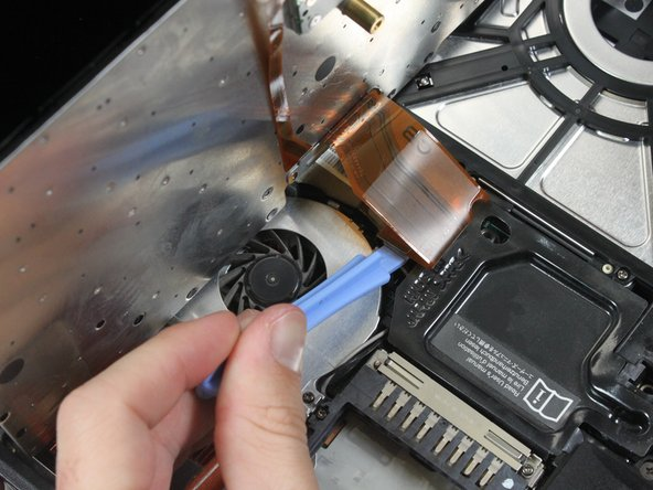 Lift the keyboard to expose the ribbon connector and lean it against the computer screen to keep the ribbon intact.