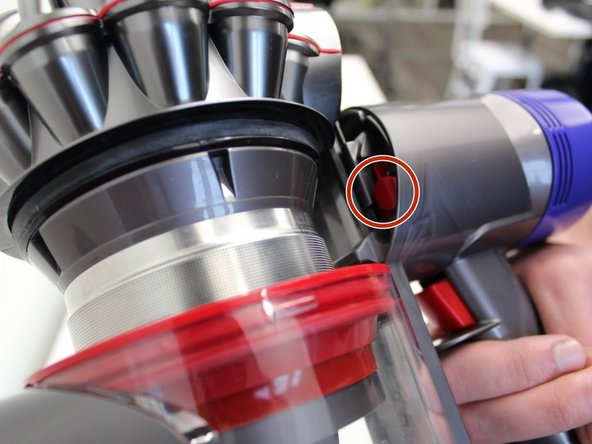 While holding the disposal tab, press on the red button within the device.