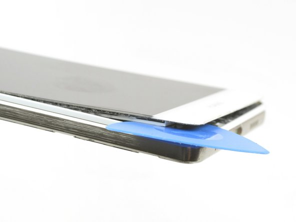 Slowly but constantly lift the bottom part of the display to get underneath the screen and further loosen the adhesive.